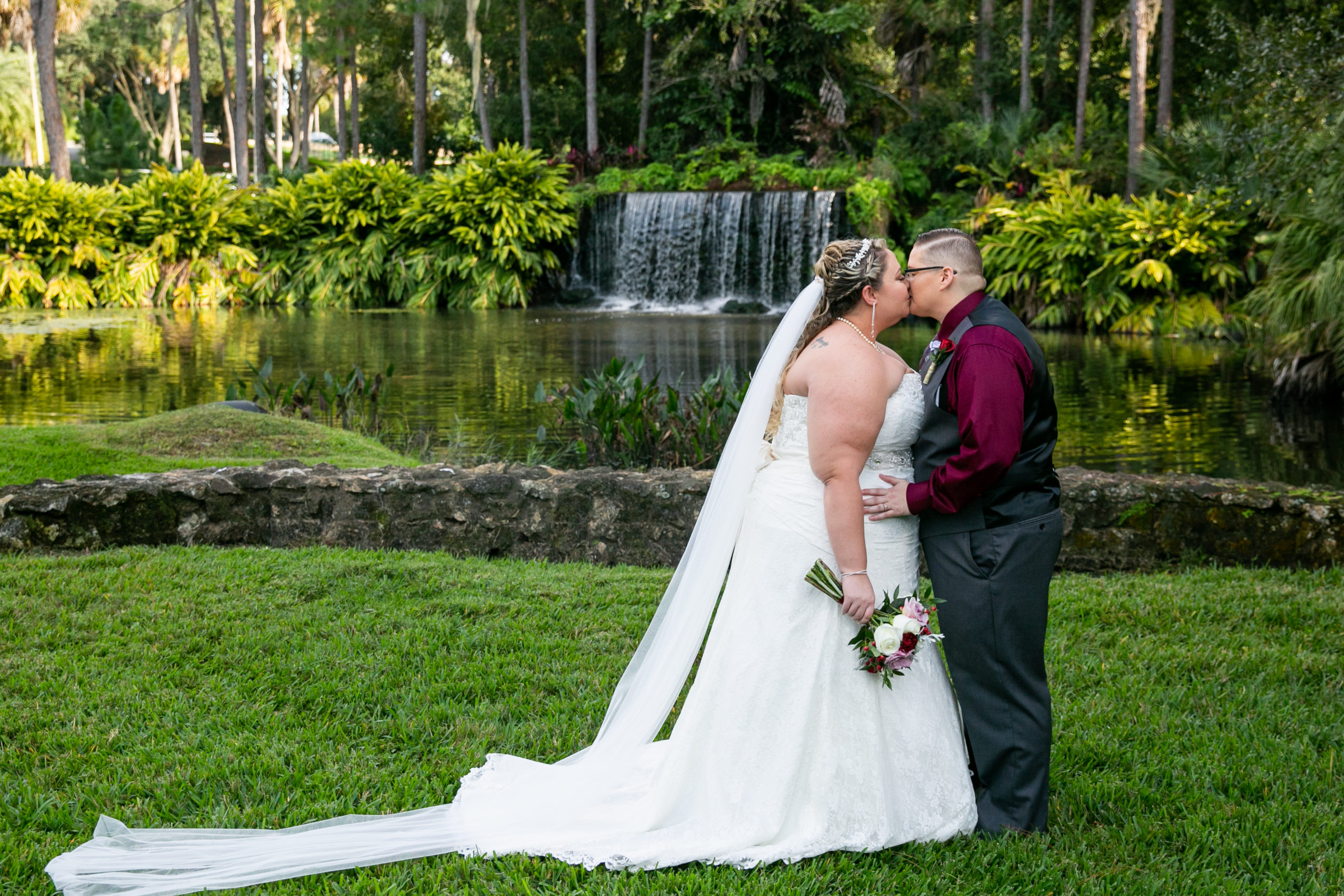 brides kissing in front of waterfall