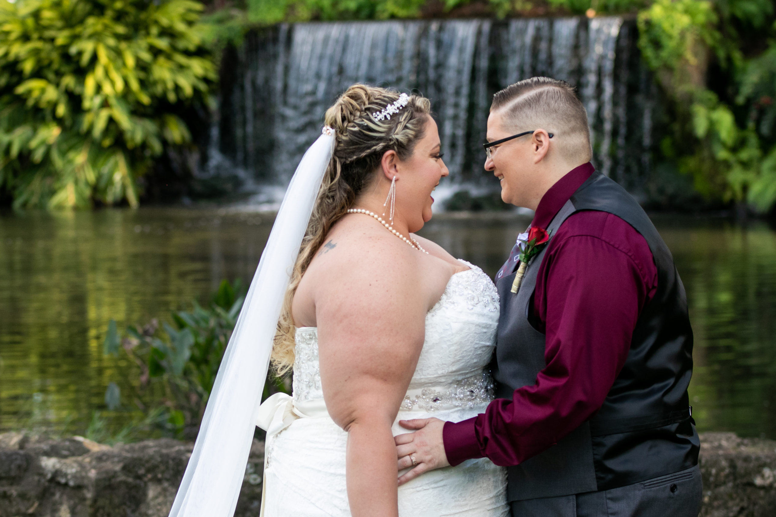 brides holding each other in front of waterfall