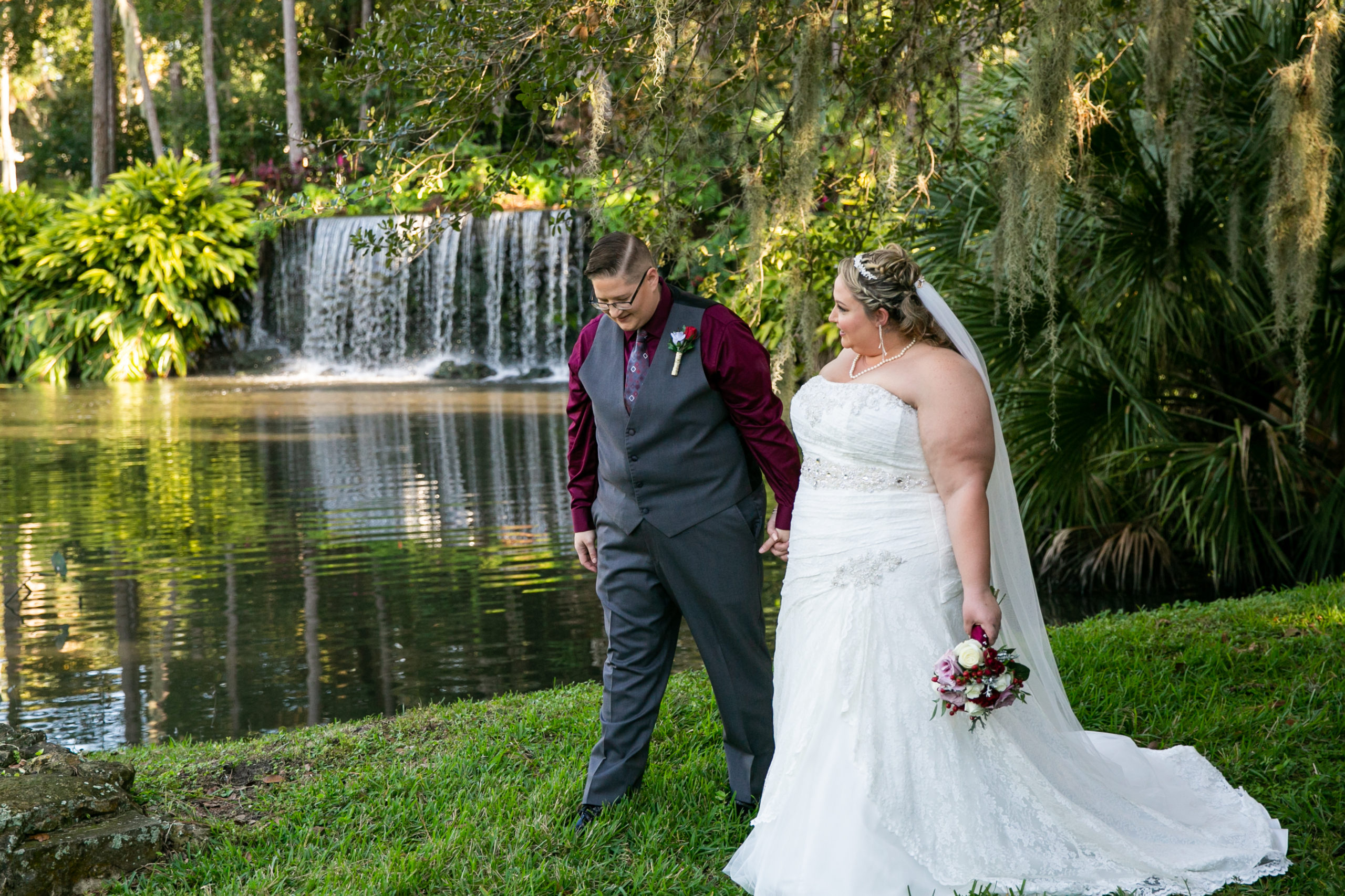 brides walking hand in hand in front of waterfall before vineyard inspired wedding ceremony
