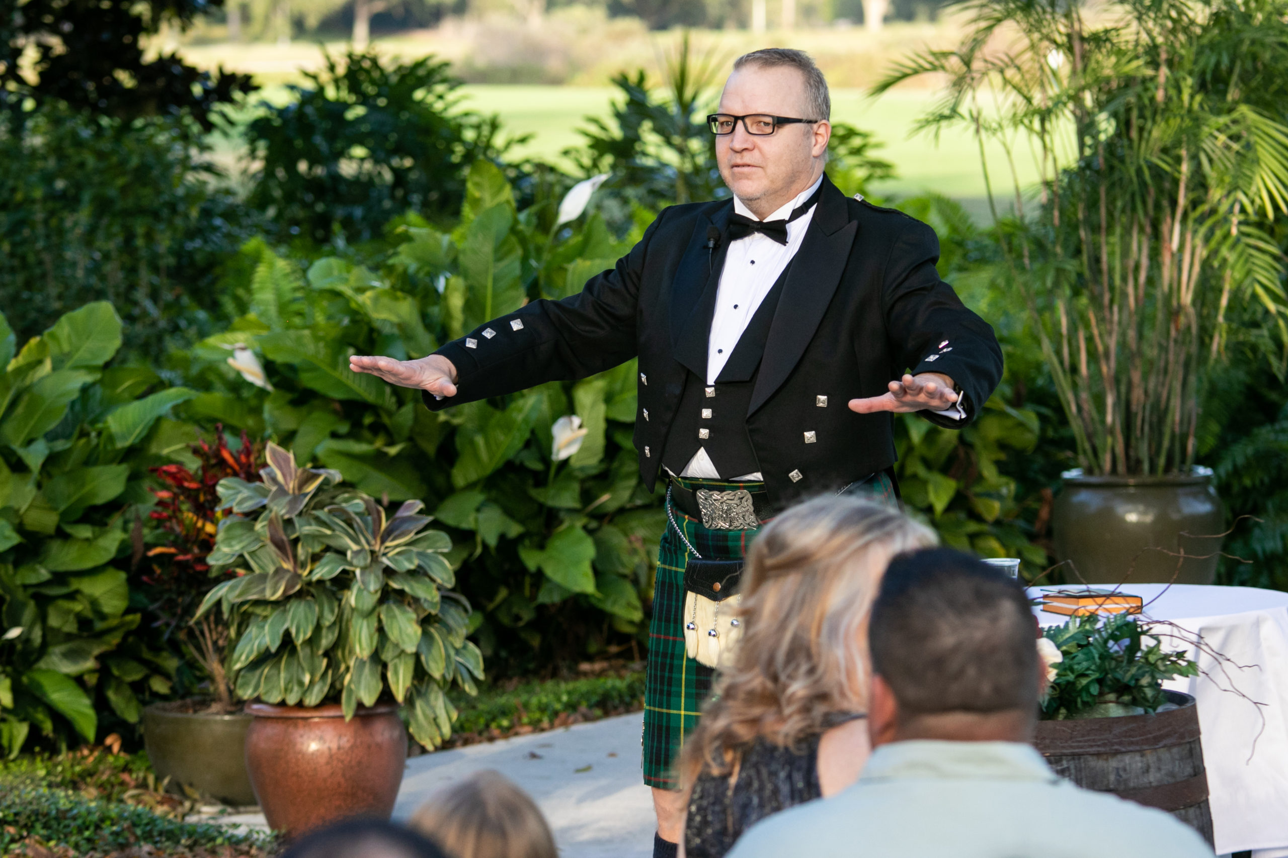 officiant in kilt telling wedding guests to be seated for vineyard inspired wedding