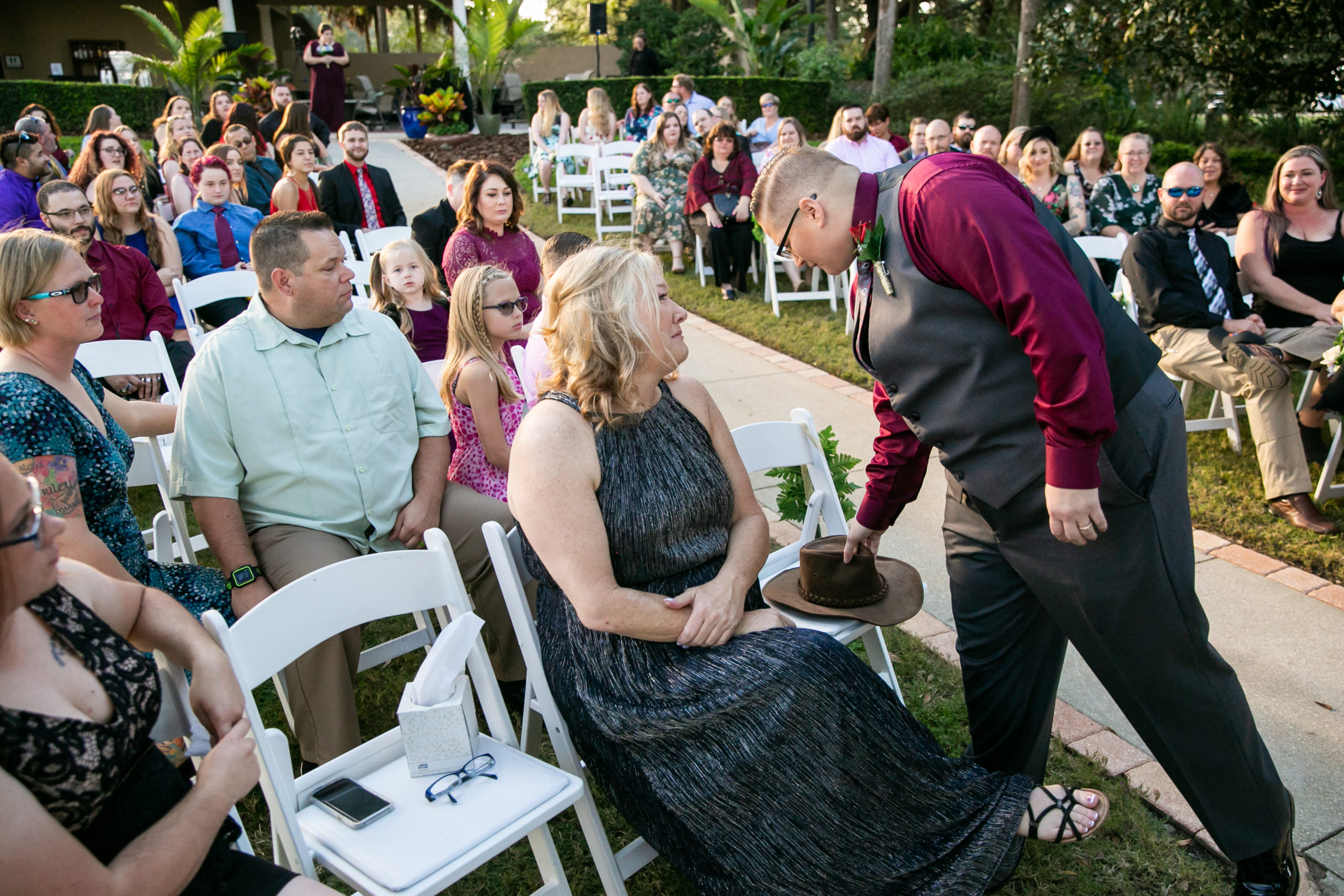 bride placing dad's leather hat over vacant ceremony seat for vineyard inspiring wedding