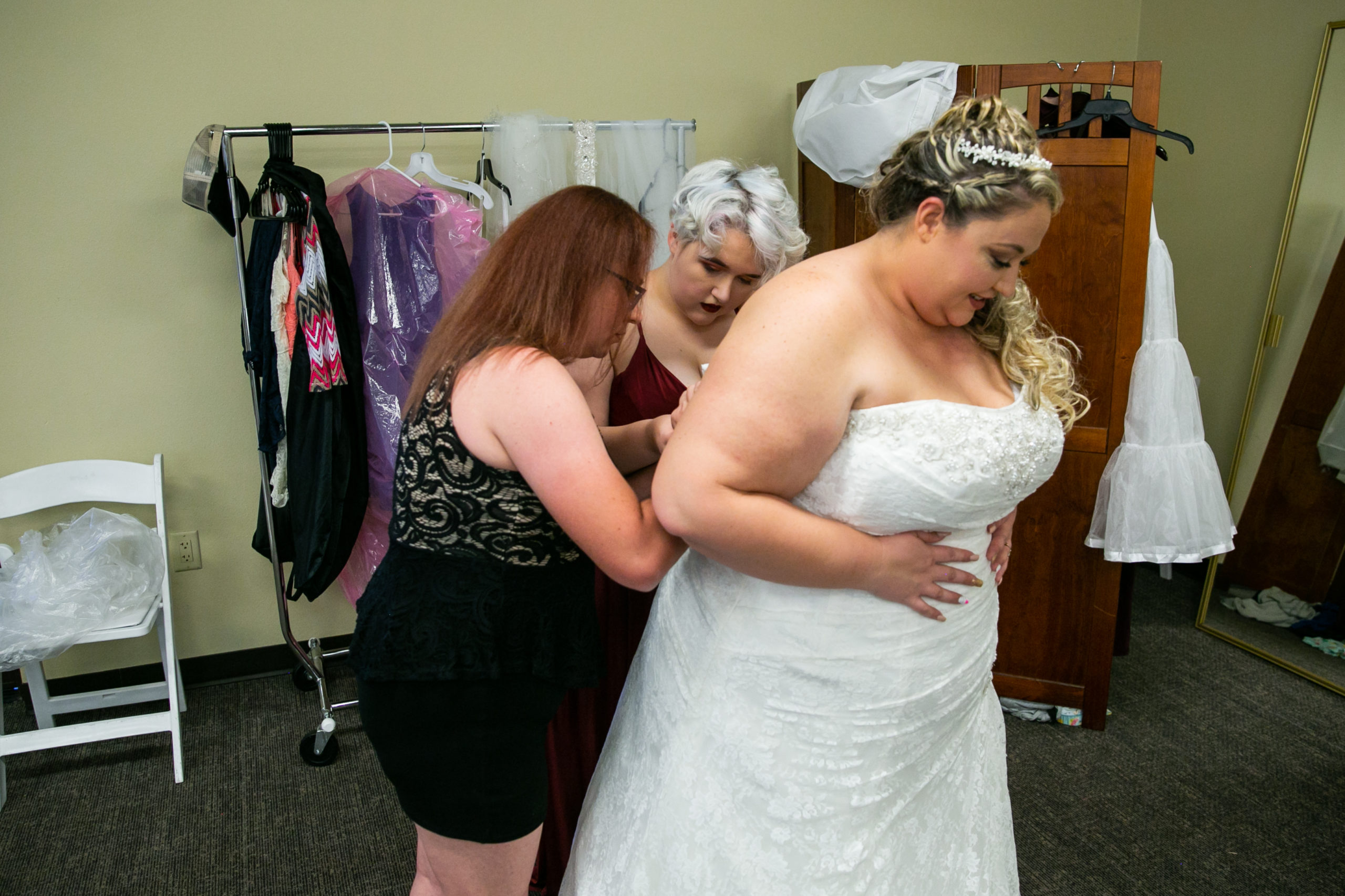 Bride getting her dress put on by her daughter