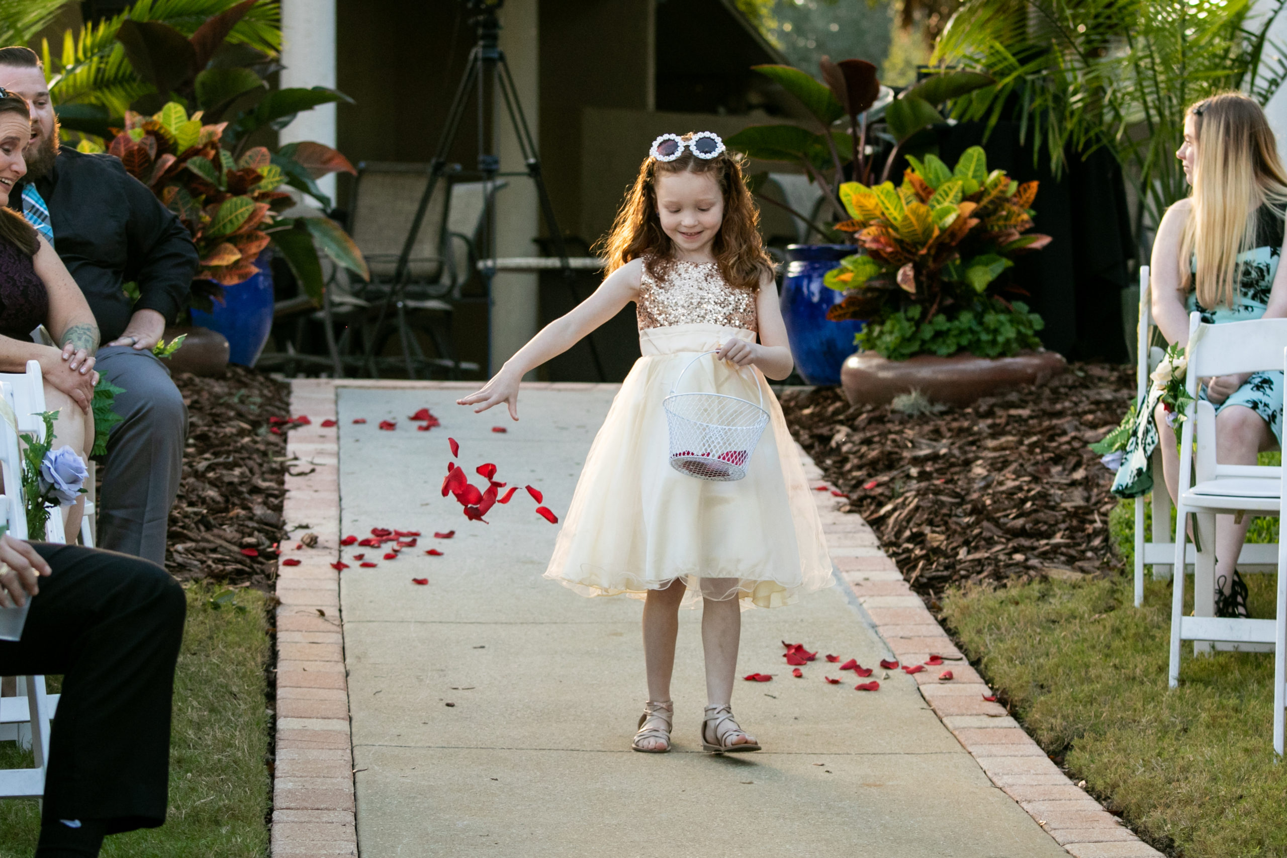 flower girl dropping rose petals down the aisle for vineyard inspired wedding