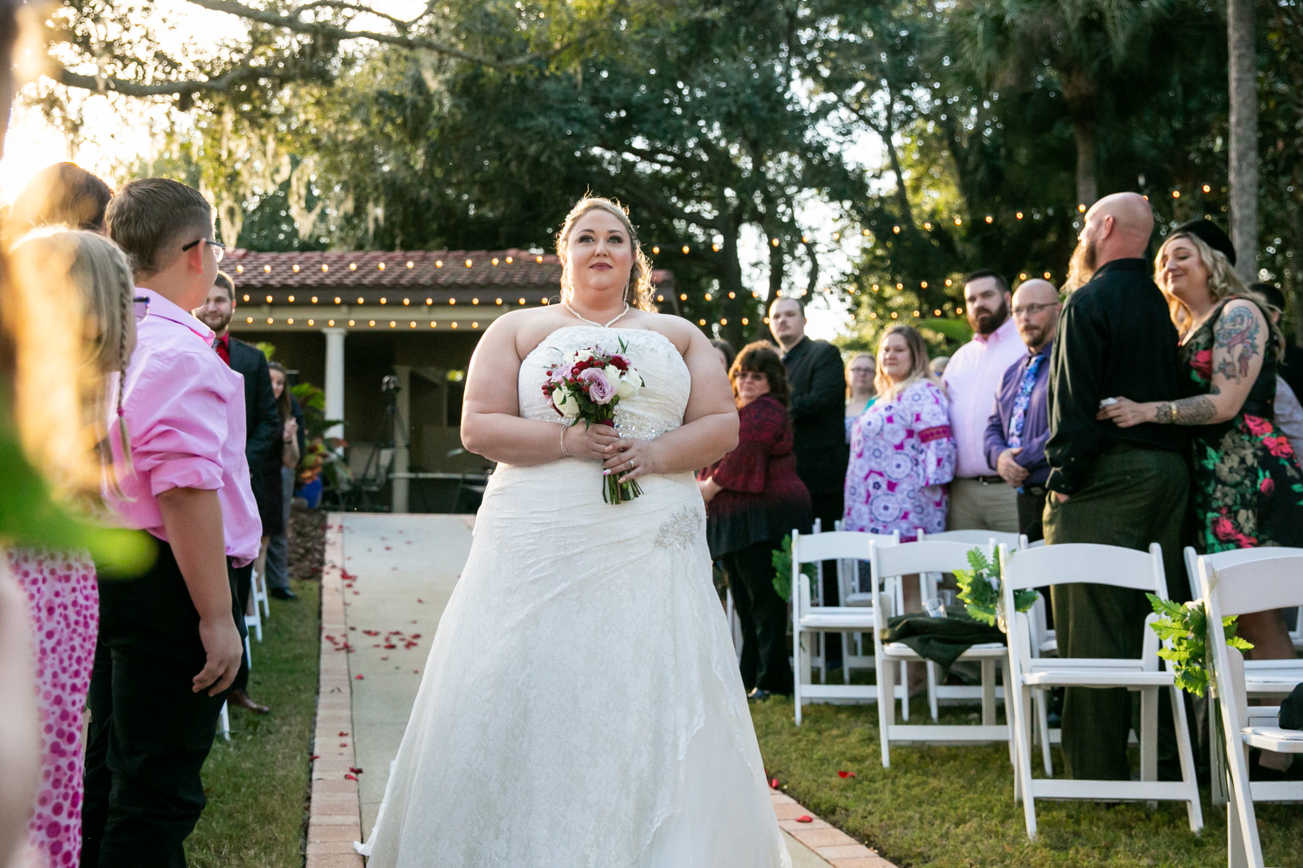 bride walking down the aisle with guests watching ceremony