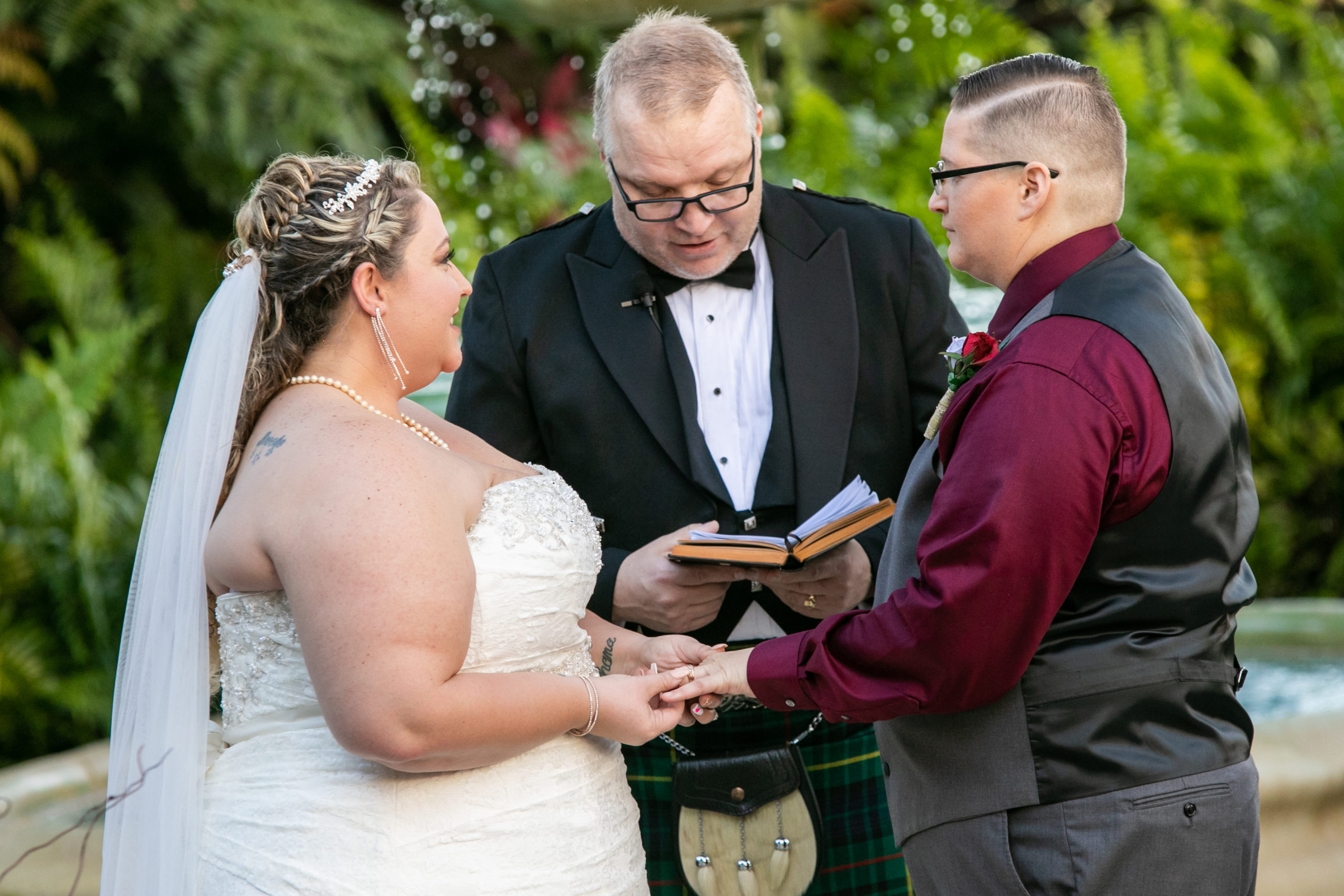 Officiant presiding over wedding with two brides