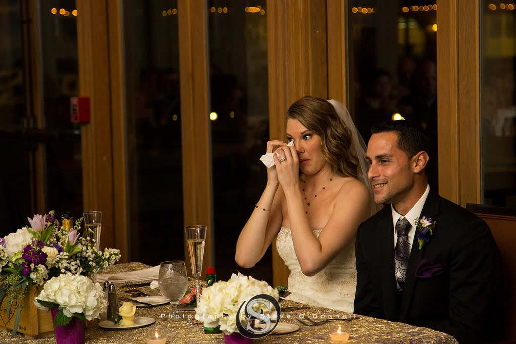 Bride and groom sitting as bride wipes tears from her eyes