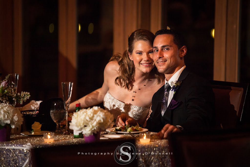 bride and groom smiling at sweetheart table for photo