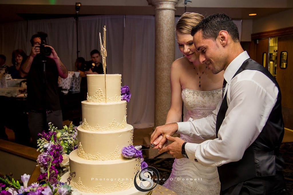 bride and groom cutting peacock wedding cake