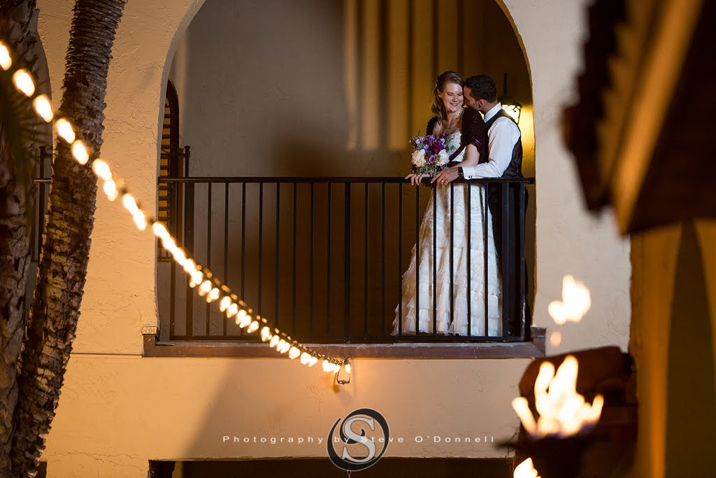 bride and groom kissing on balcony with market lighting