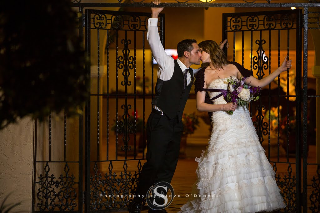 Bride and groom in front of iron gates at Mission Inn in Florida