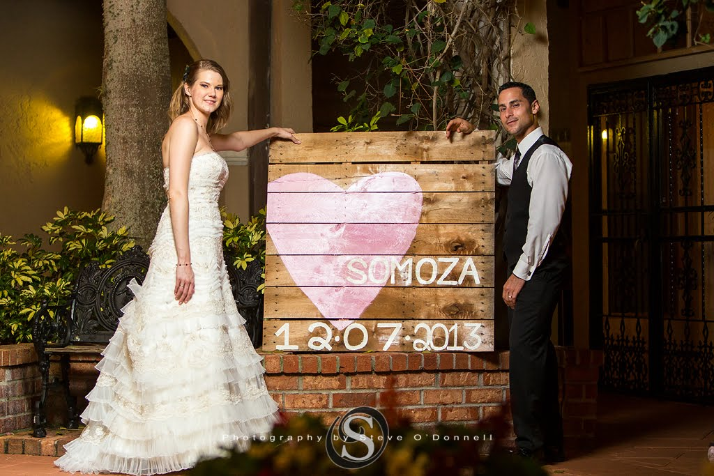 Bride and Groom standing next to wedding sign