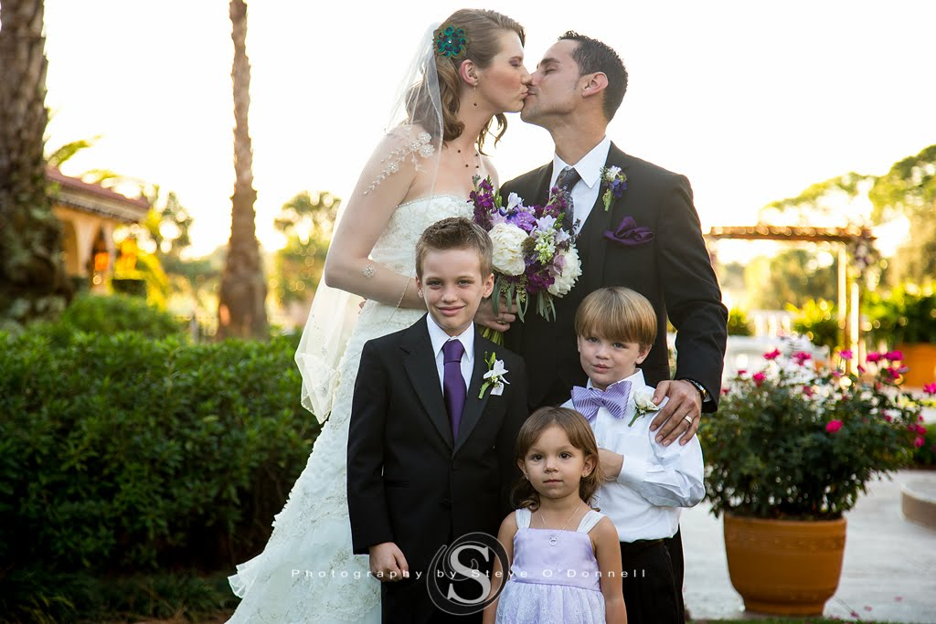 Bride and Groom kissing with ring bearers and flower girls in front