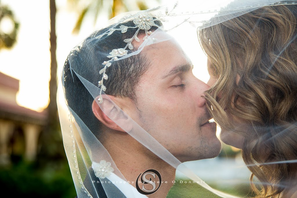 bride and groom portrait kissing under veil
