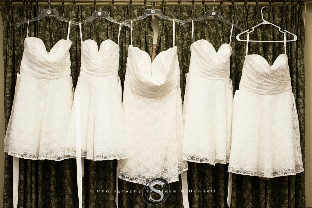 five white bridesmaids dresses hanging