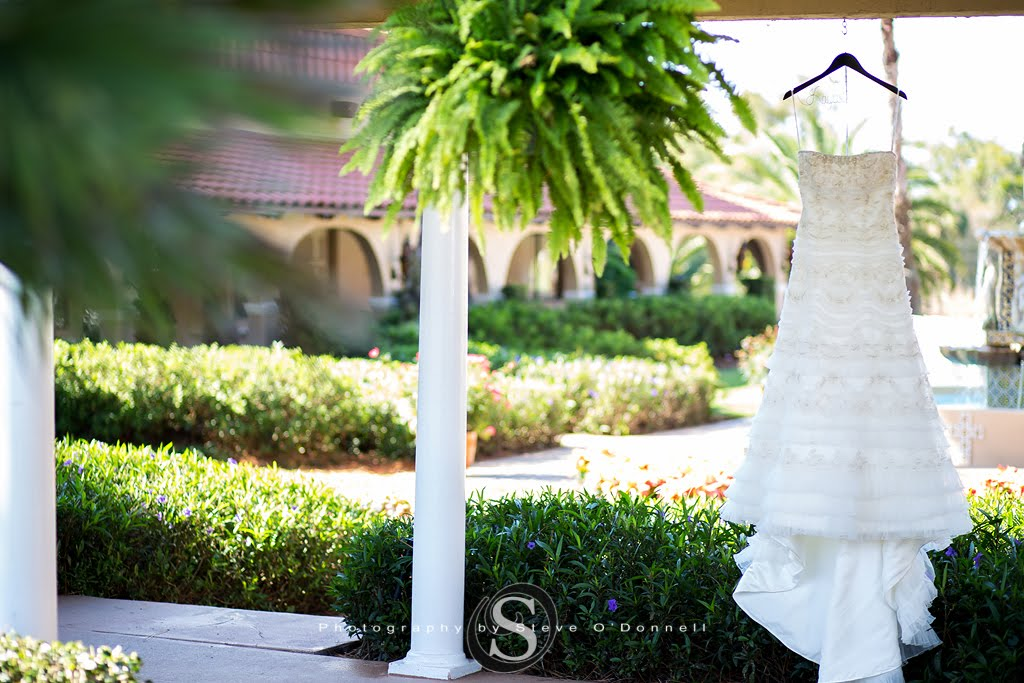 brides dress hanging in a courtyard at a florida wedding venue