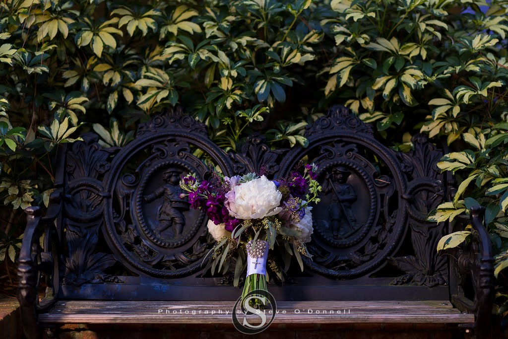 Purple Peacock Wedding bridal bouquet on an iron bench