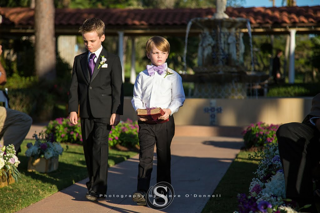 Two ring bearers walking down aisle with purple ties for peacock wedding