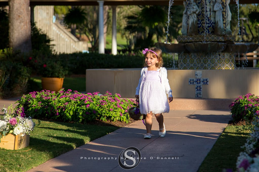 Flower girl walking down the aisle holding basket