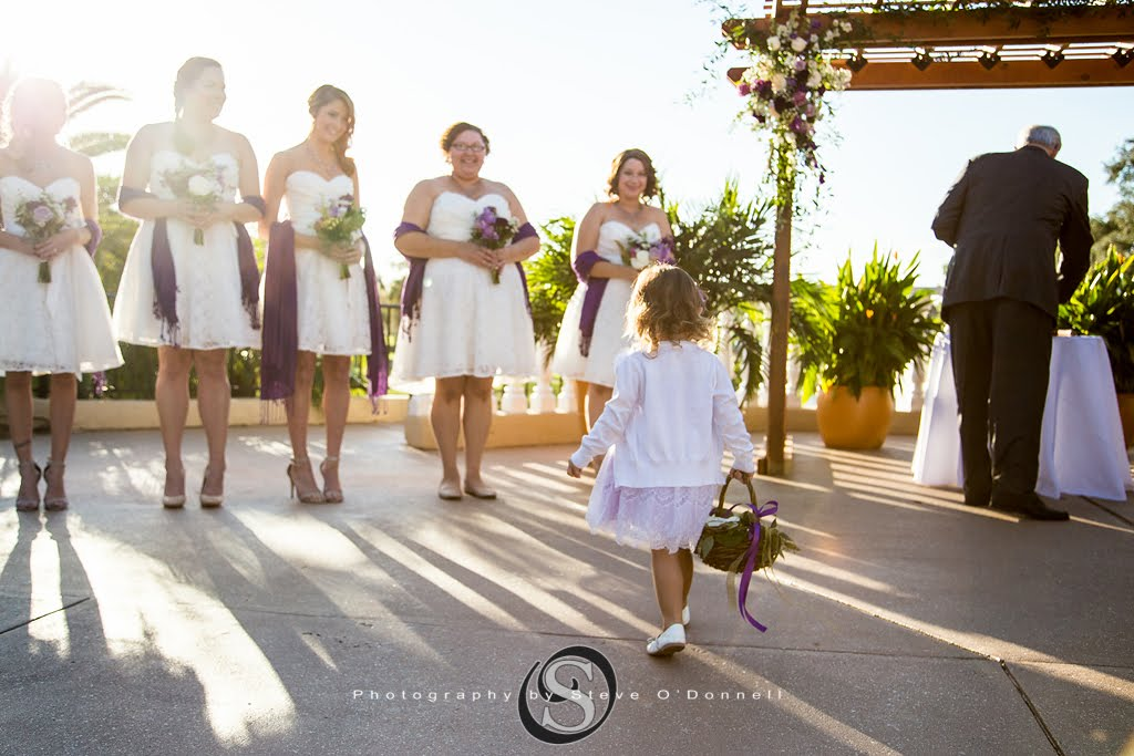 flower girl approaching bridesmaids all in white with purple sashes