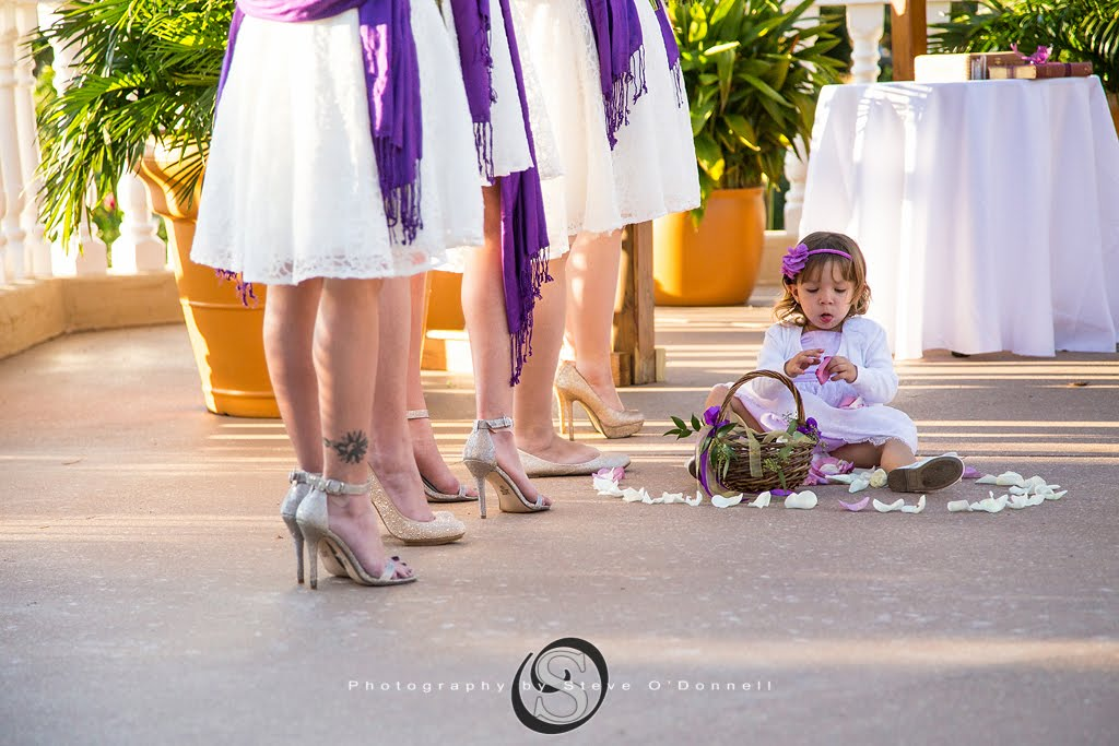 bottom of bridesmaids dresses with purple sash watching ceremony as flower girl sits on the ground and plays with petals