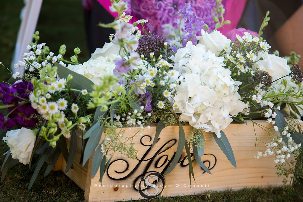 flower box that says hope with purple and white flowers for peacock wedding