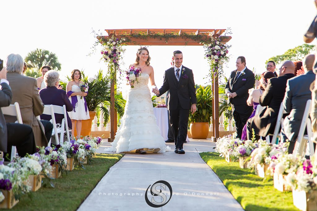 bride in white dress holding purple flowers in one hand and her grooms hand in the other