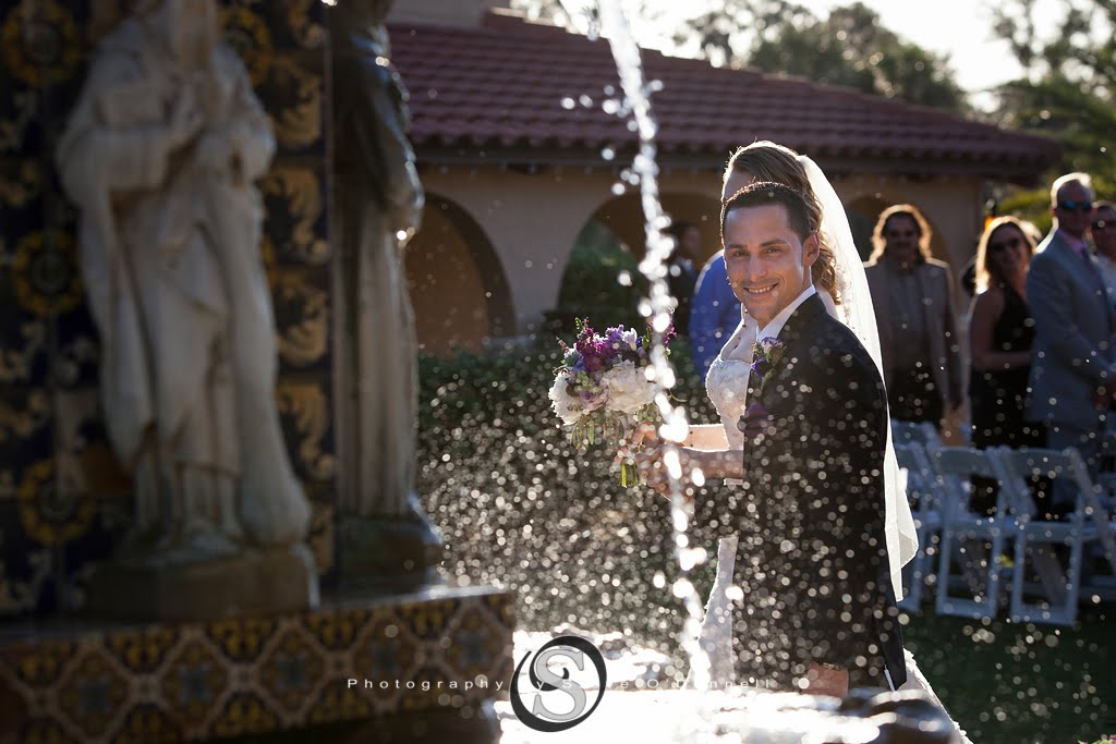 Groom looking through splashing water on fountain at plaza de la fontana in Florida