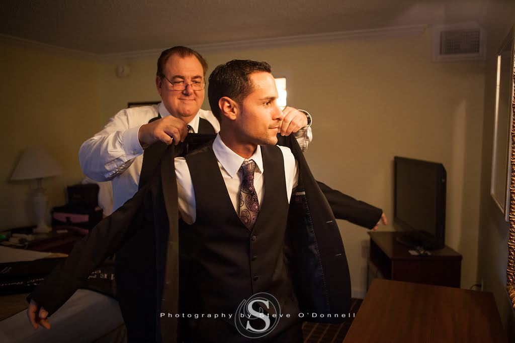 Father of groom helping his son put on his jacket to get ready for his peacock wedding in florida