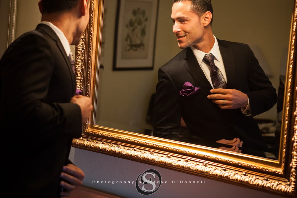 Groom admiring his purple pocket handkerchief before his peacock wedding