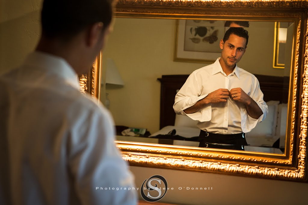 Groom buttoning his shirt in a mirror