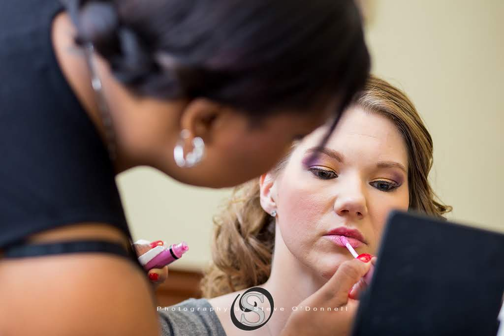 Bride getting lip gloss applied on wedding day