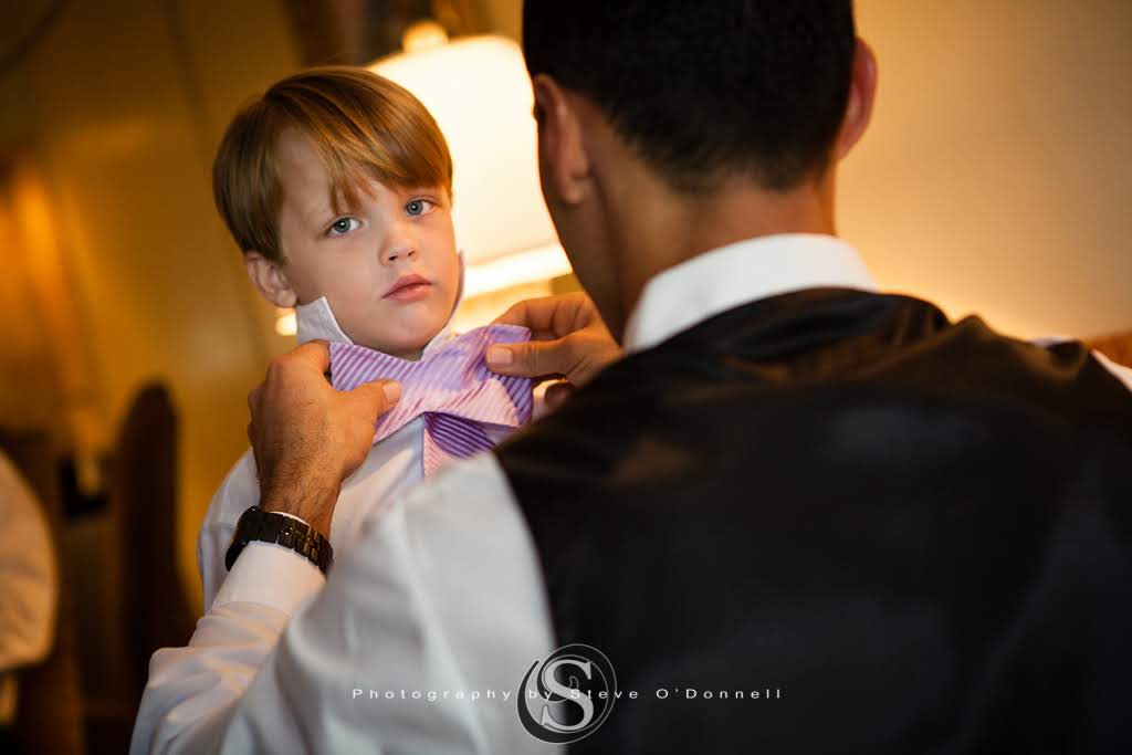 Groom helping ring bearer tie a bowtie