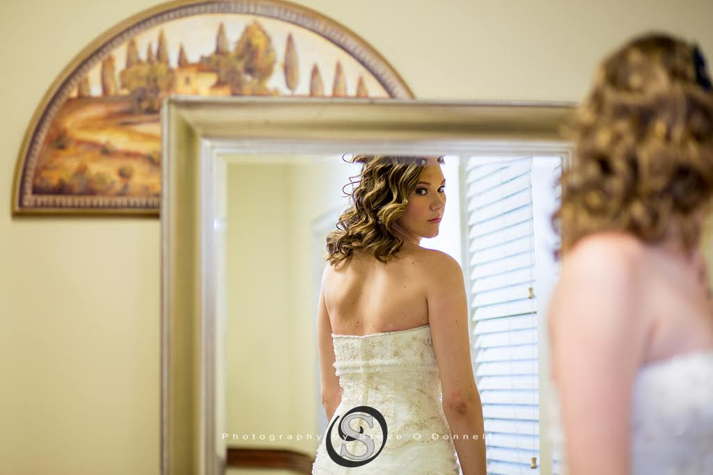 Bride looking in the mirror at the back of her dress