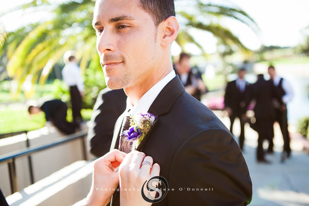 Groom getting boutonniere placed