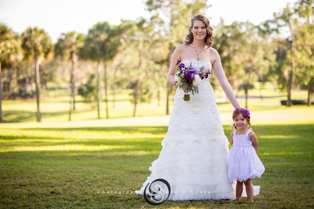 Bride holding purple floral on Florida golf course with her flower girl