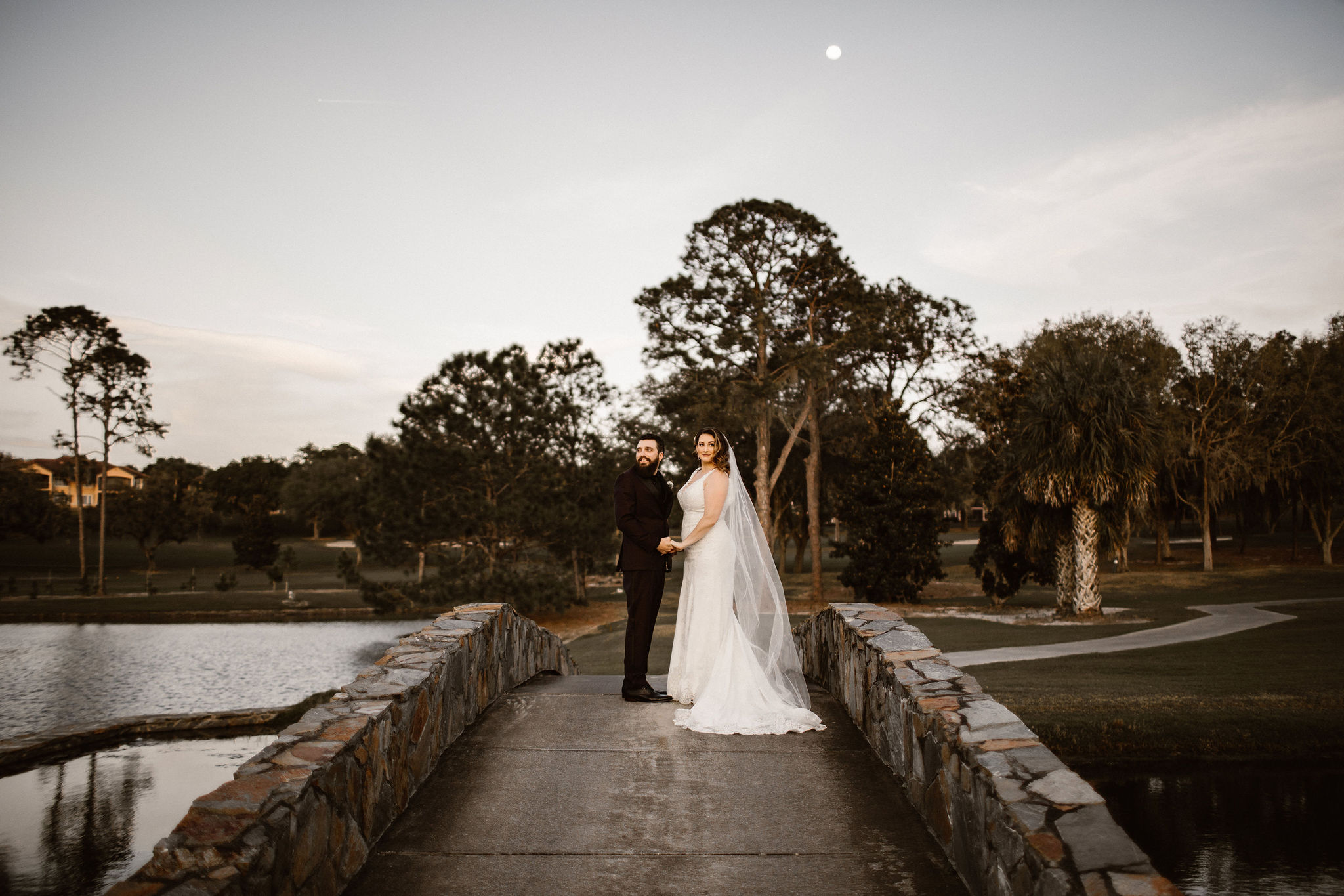 Bride and Groom on Bridge with Full Moon in Distance