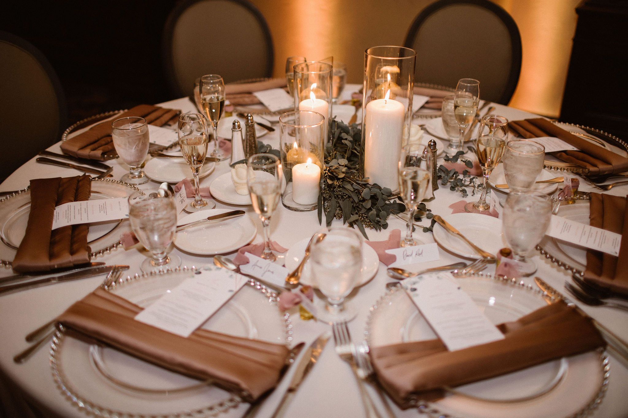 wedding table setting with glass chargers and mauve napkins