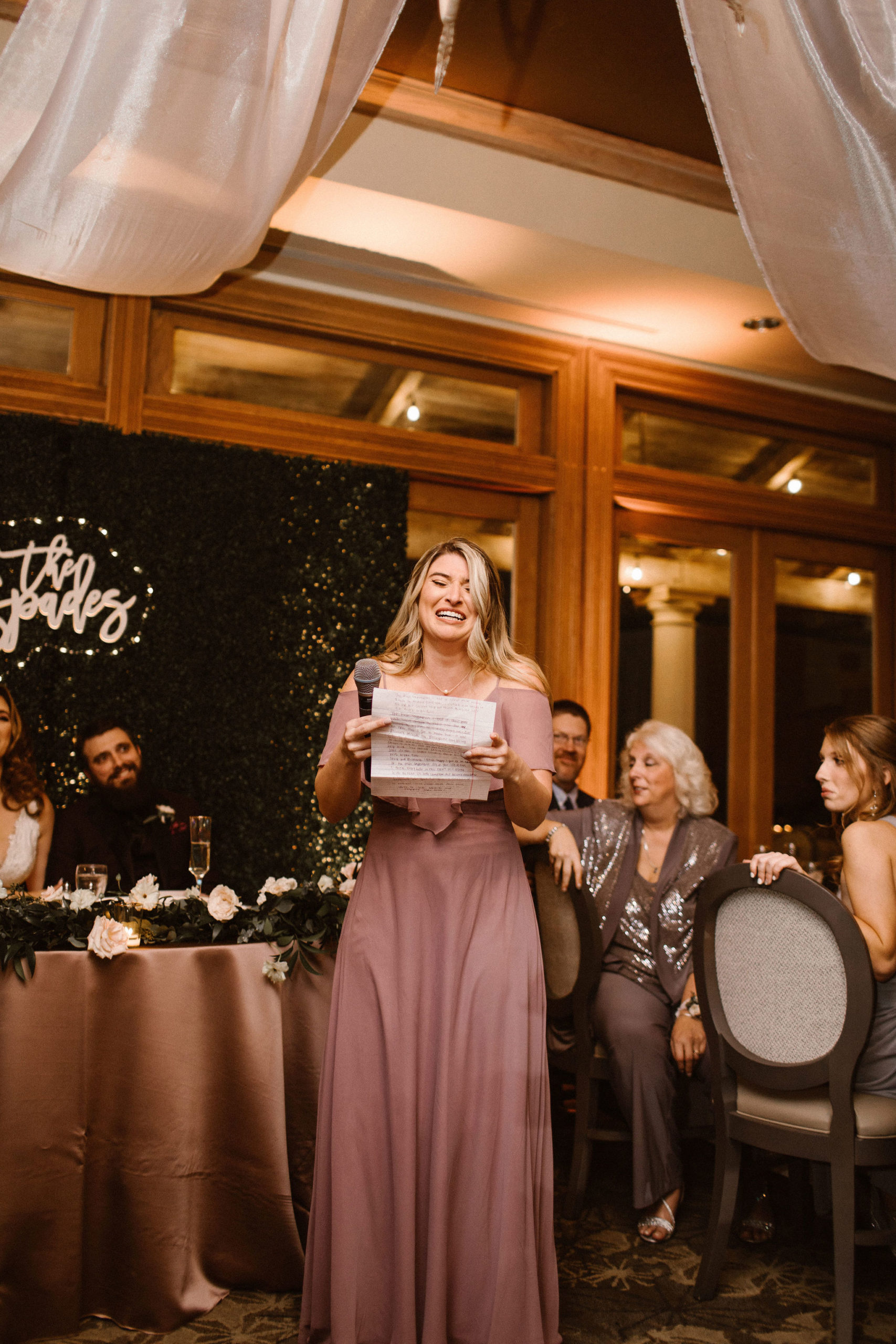 Bridesmaid in mauve dress giving speech to bride and groom