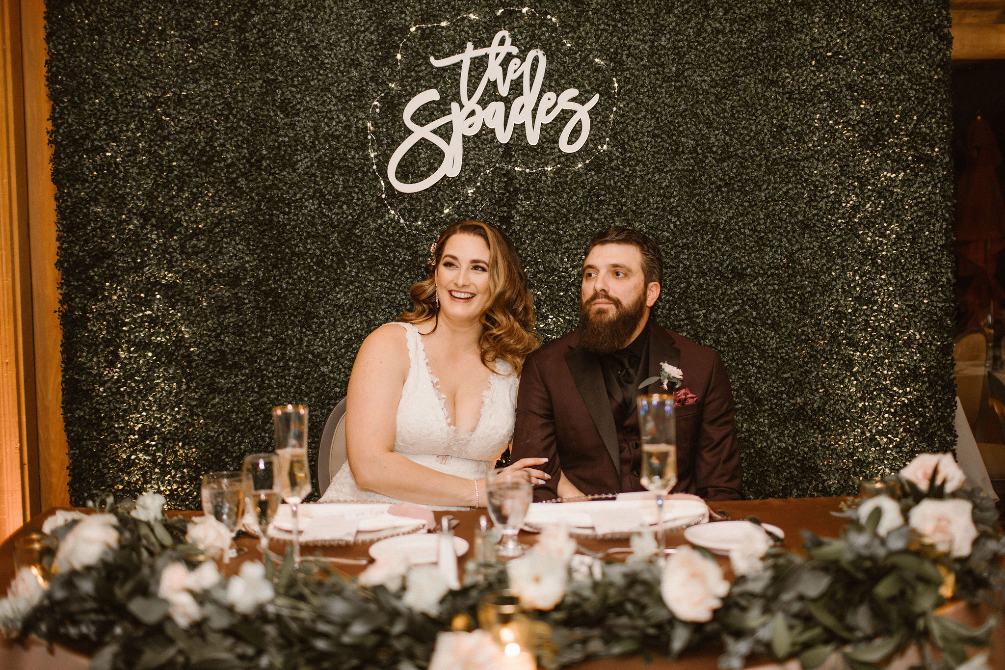 bride and groom sitting at muave sweetheart table in front of greenery wall for wedding