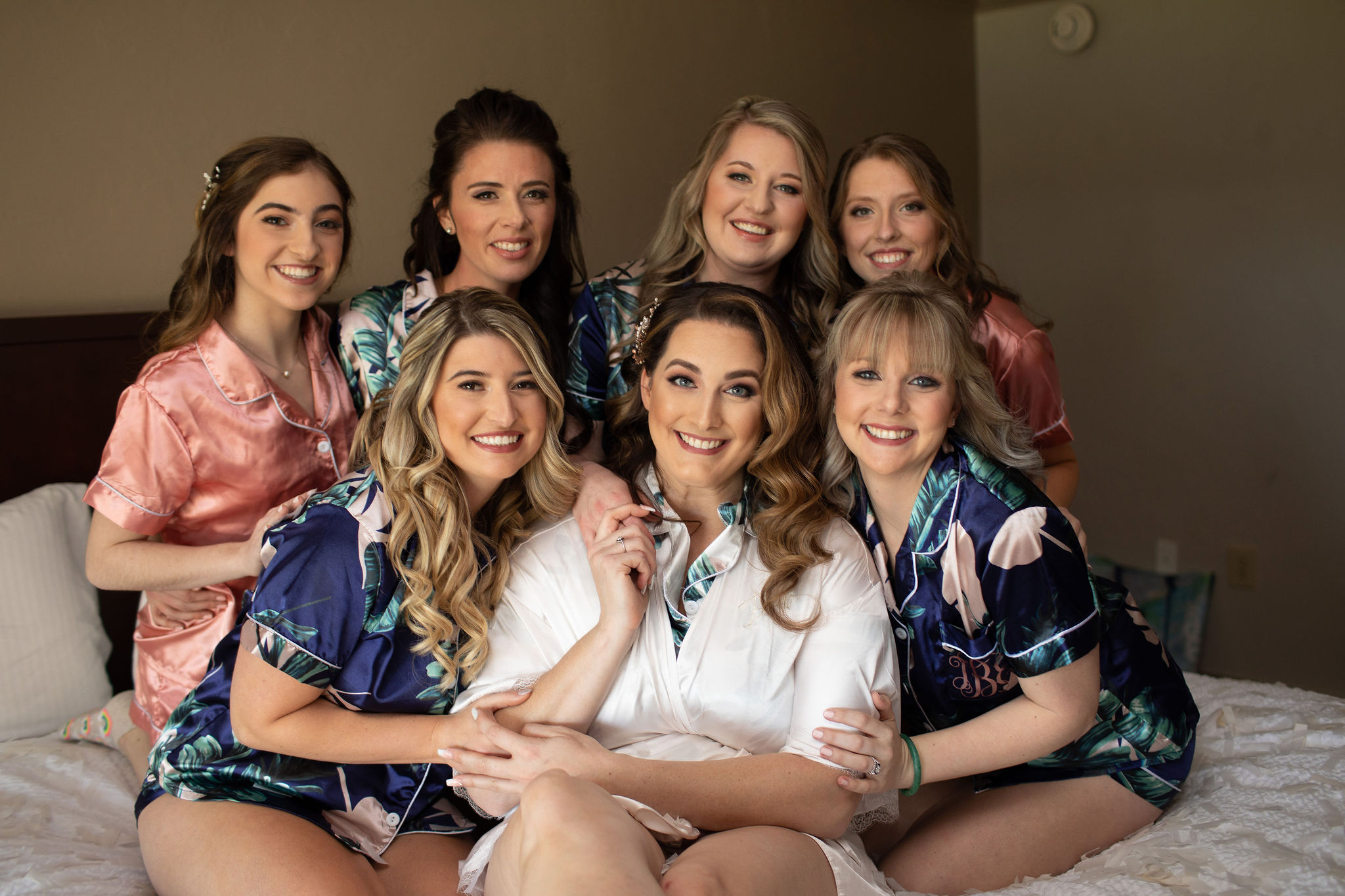 bride and her bridesmaids sitting in bed getting ready for romantic mauve wedding