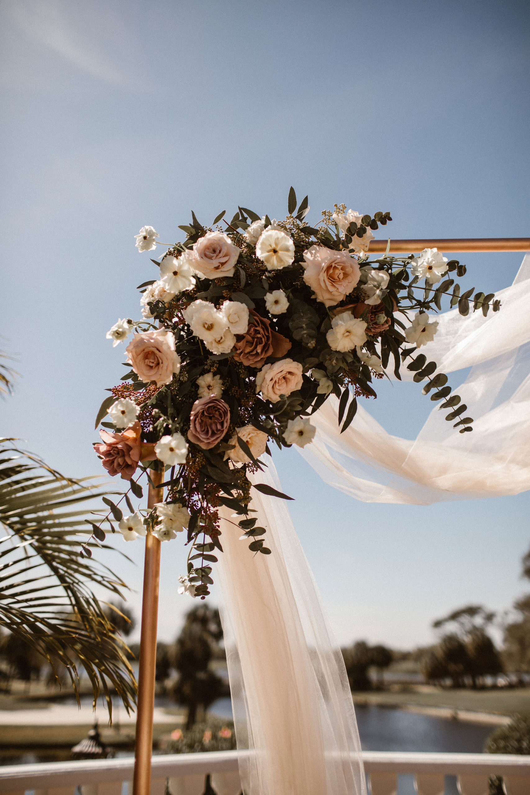 wedding arch with mauve and white floral arrangement