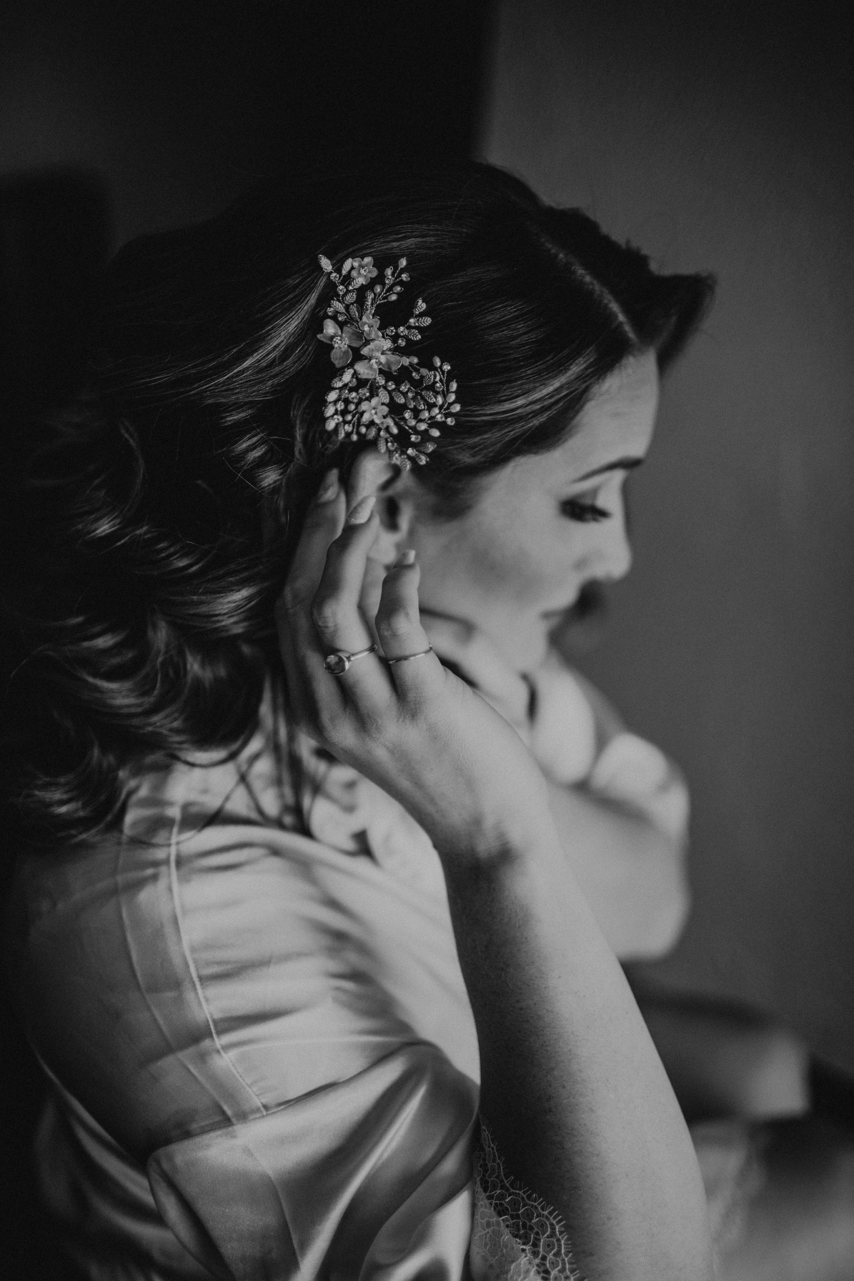 black and white photo of bride touching her hair piece for her romantic wedding