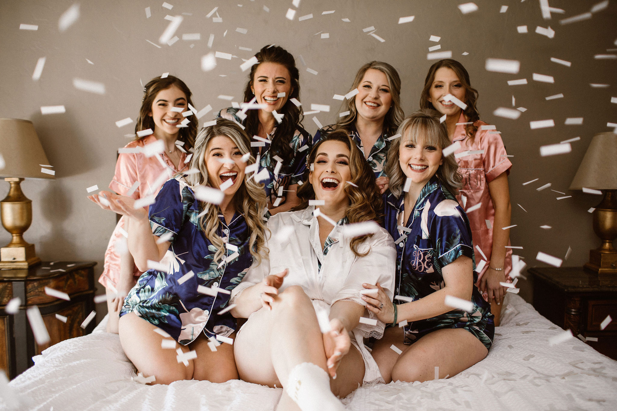 bride and her bridesmaids sitting in bed shooting off white confetti