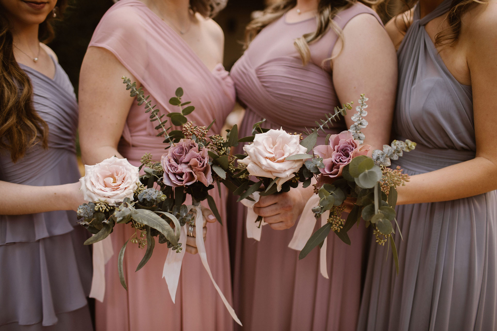 bridesmaids in mauve dresses holding their wedding bouquets