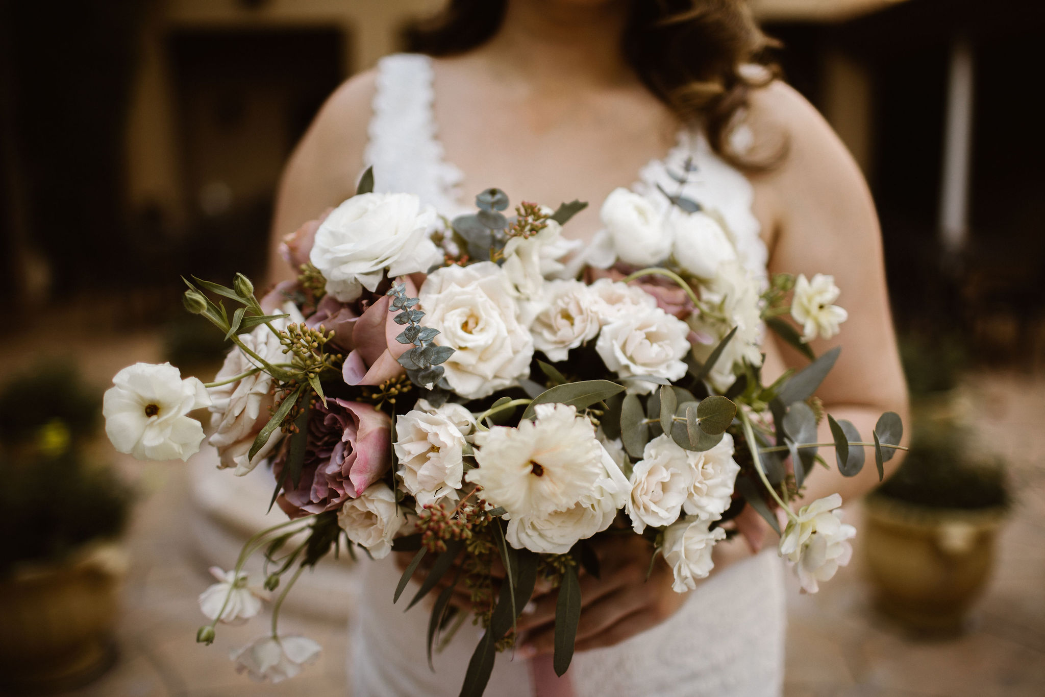 bride holding bouquet of white and mauve floral